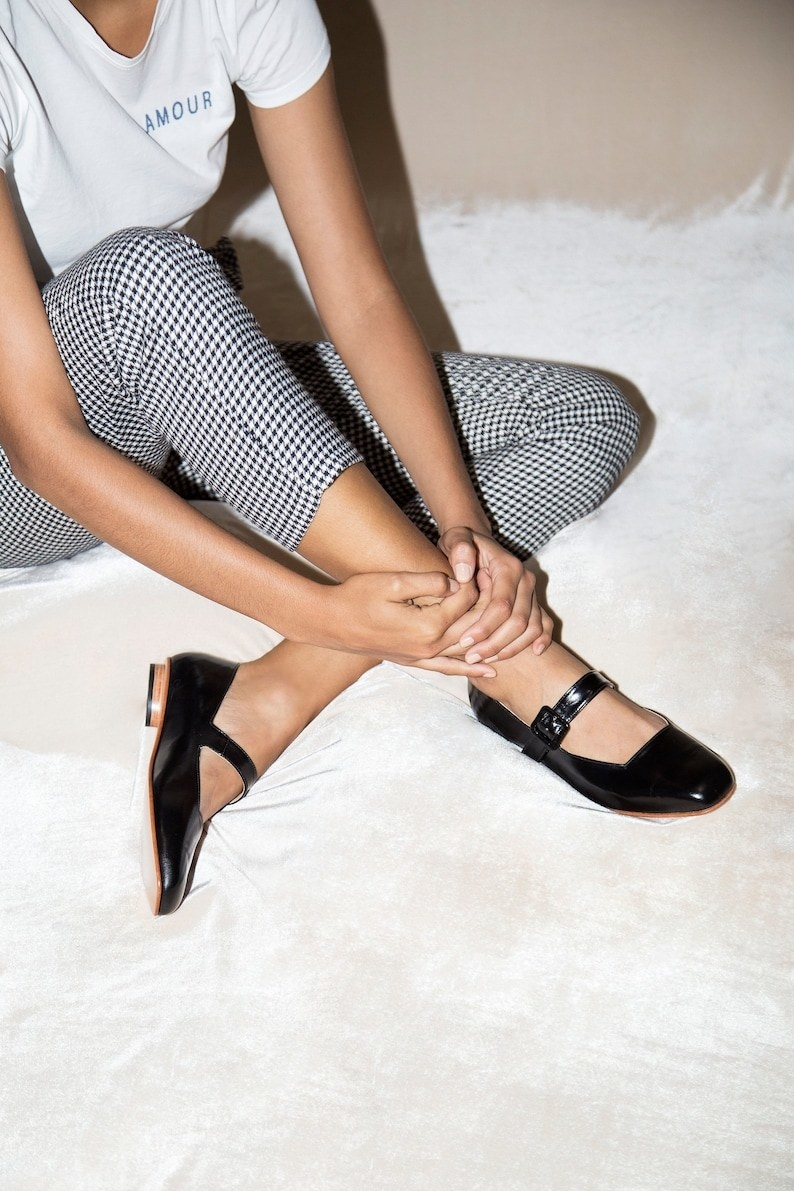 model wearing the black gloss flats with buckle across the top