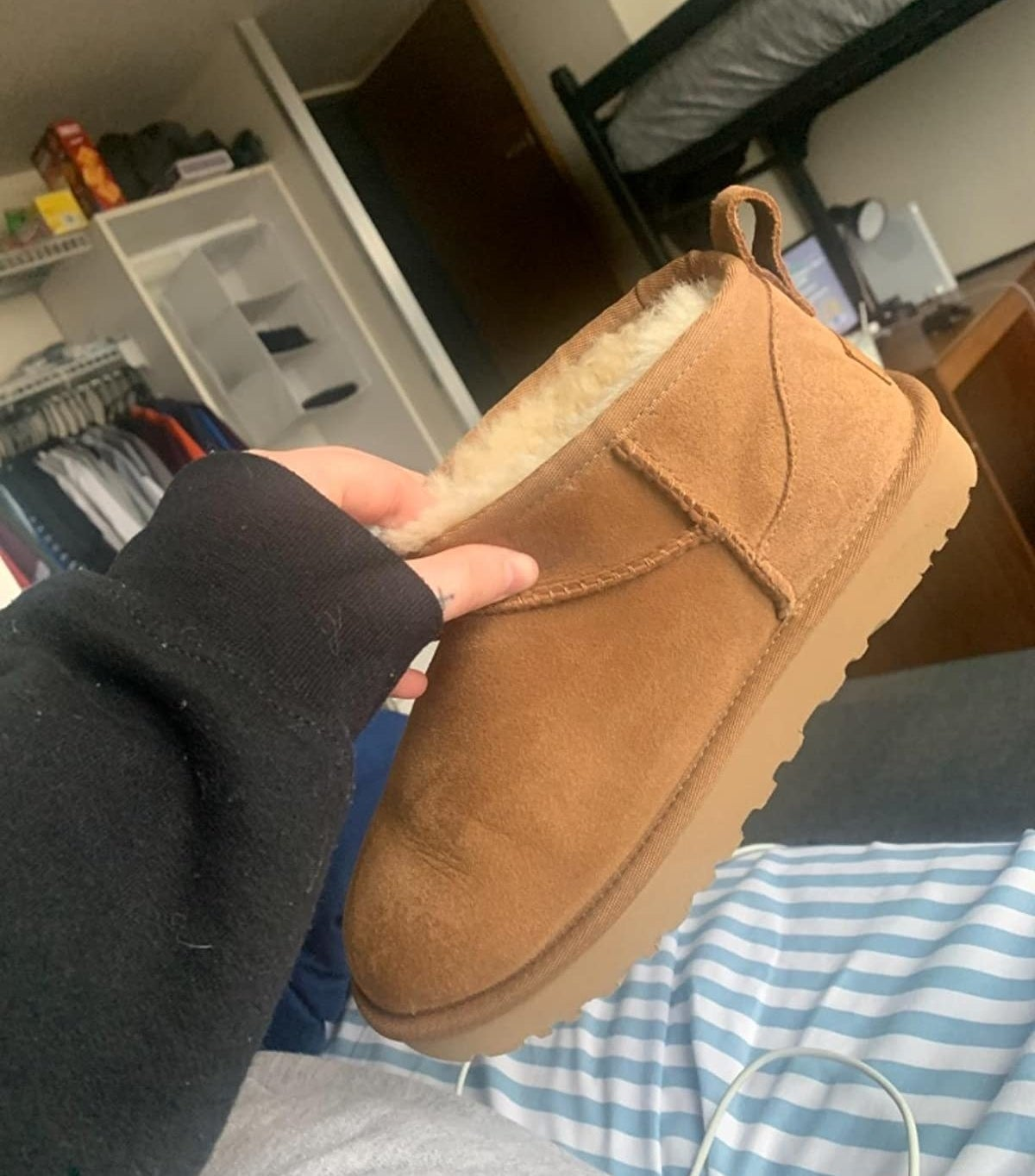 reviewer holding up a short brown Ugg boot