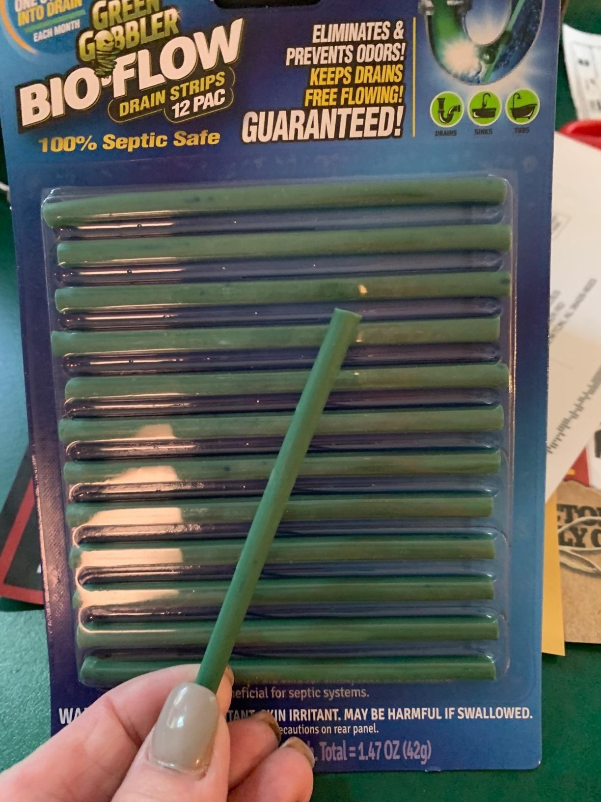 hand holds green drain deodorizer strip