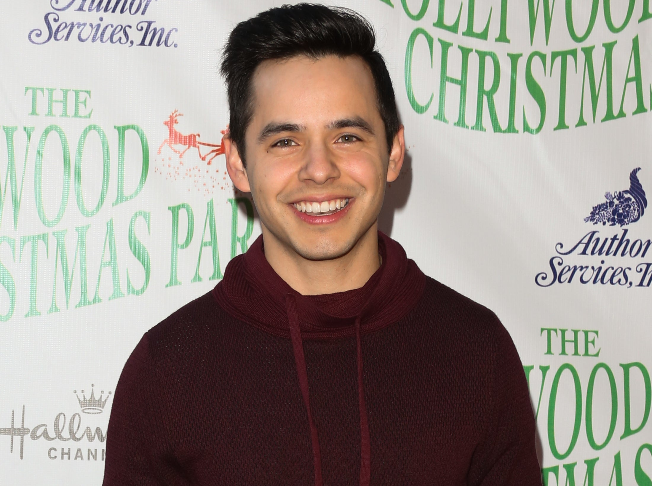 David wears a maroon hooded sweater to an event