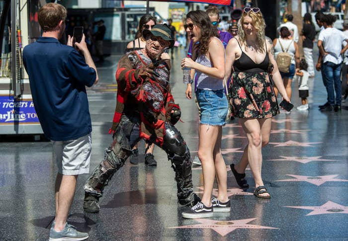 People interacting with a guy dressed as Freddy Kreuger on Hollywood Boulevard