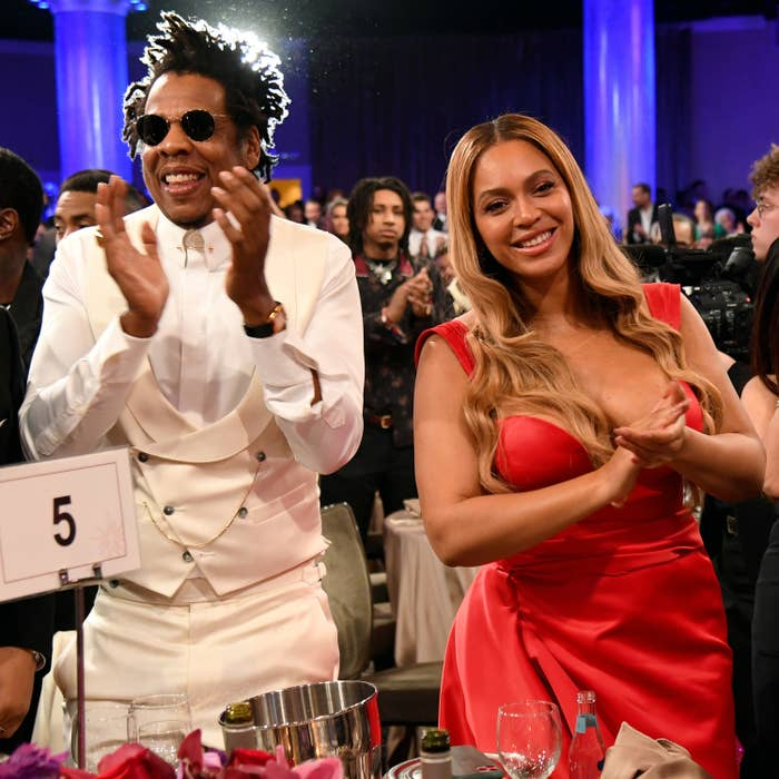 Jay Z and Beyoncé clap while standing up at their table during a pre-Grammy gala