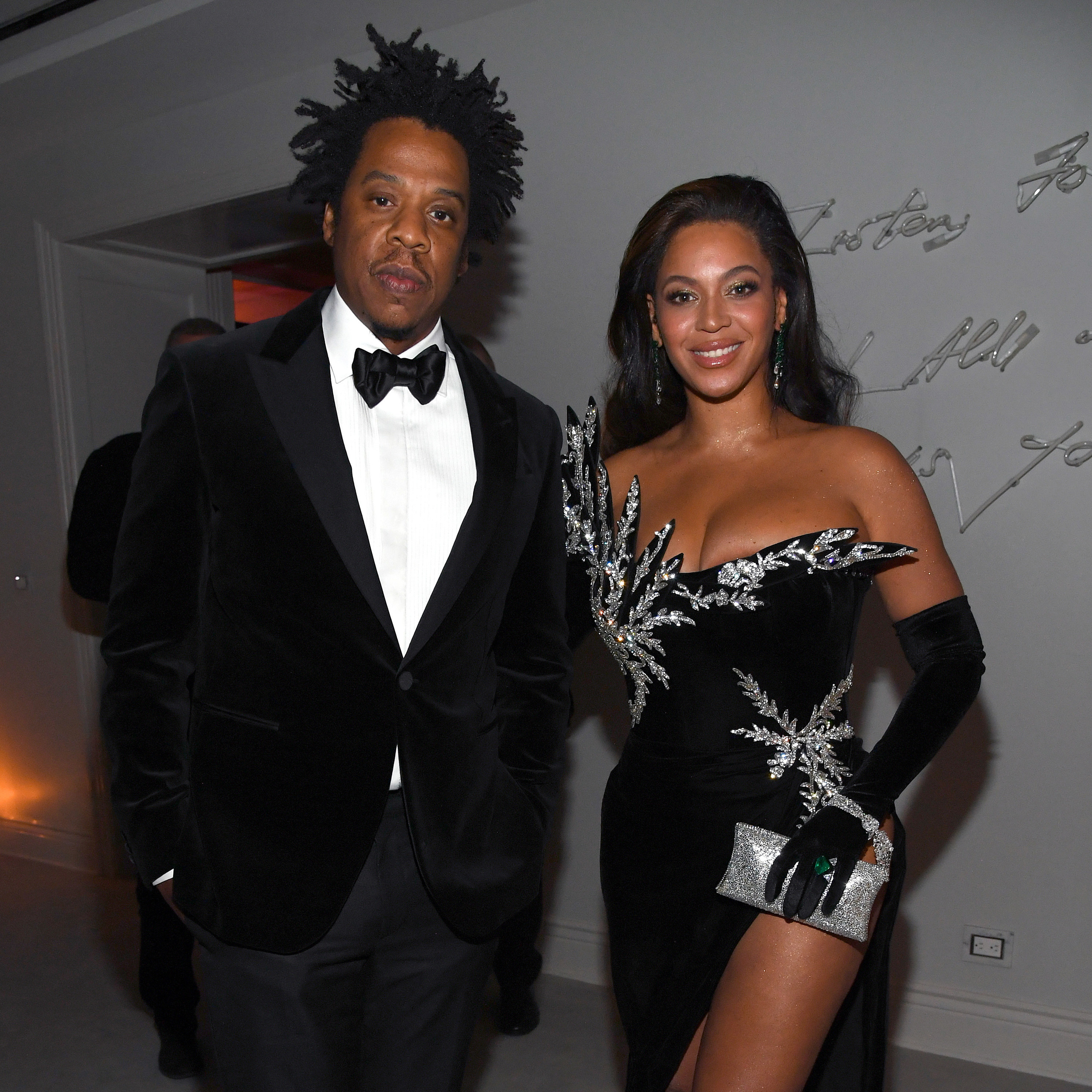 Jay-Z and Beyoncé stand next to each other at a party