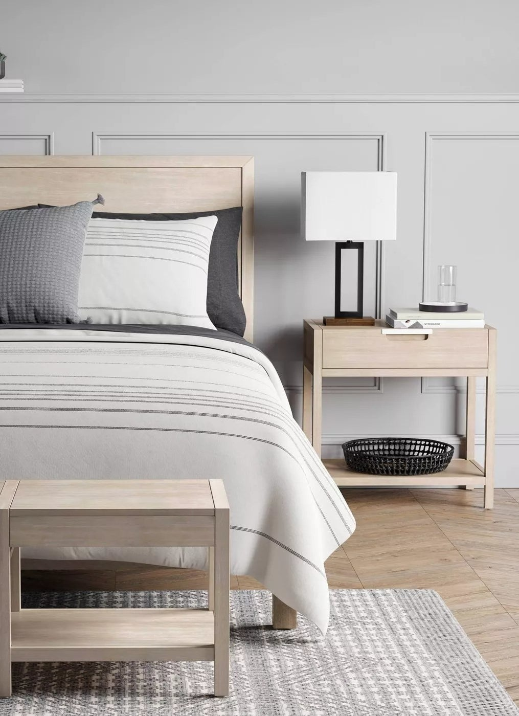 The nightstand with a drawer and open shelf underneath in a bedroom