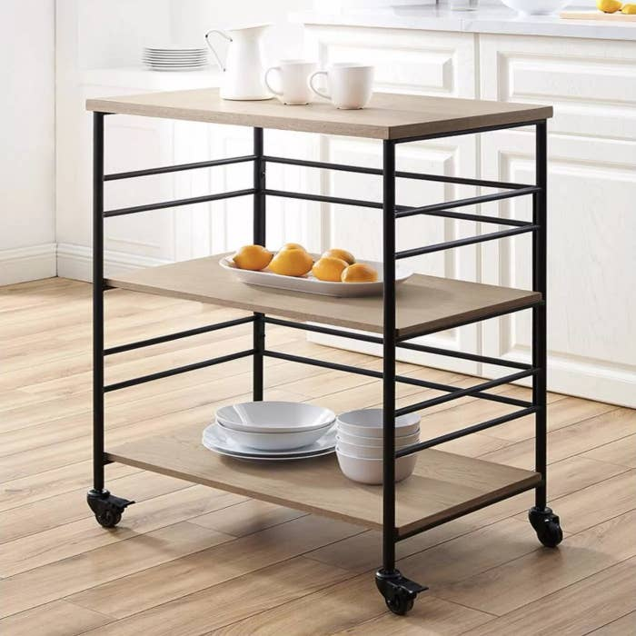 The kitchen cart on wheels holding dishes