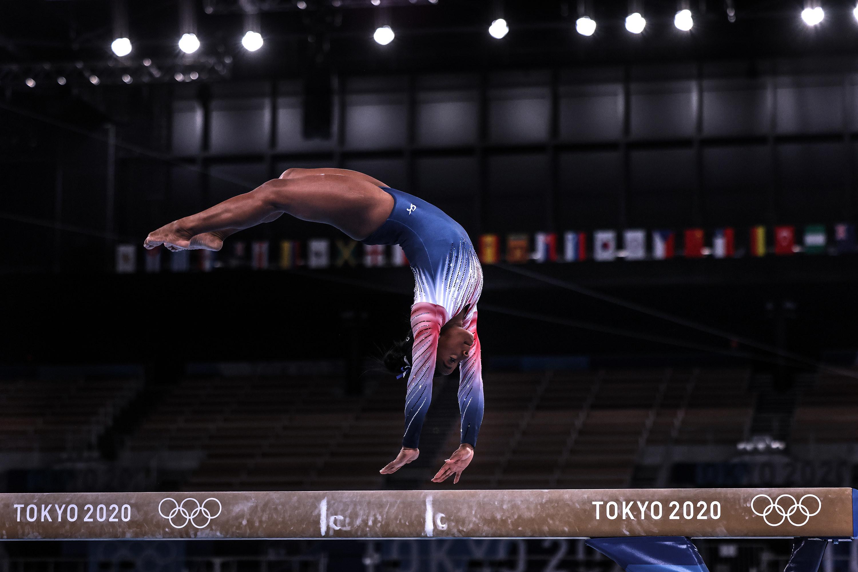 Simone Biles springs upside down on her hands on the balance beam