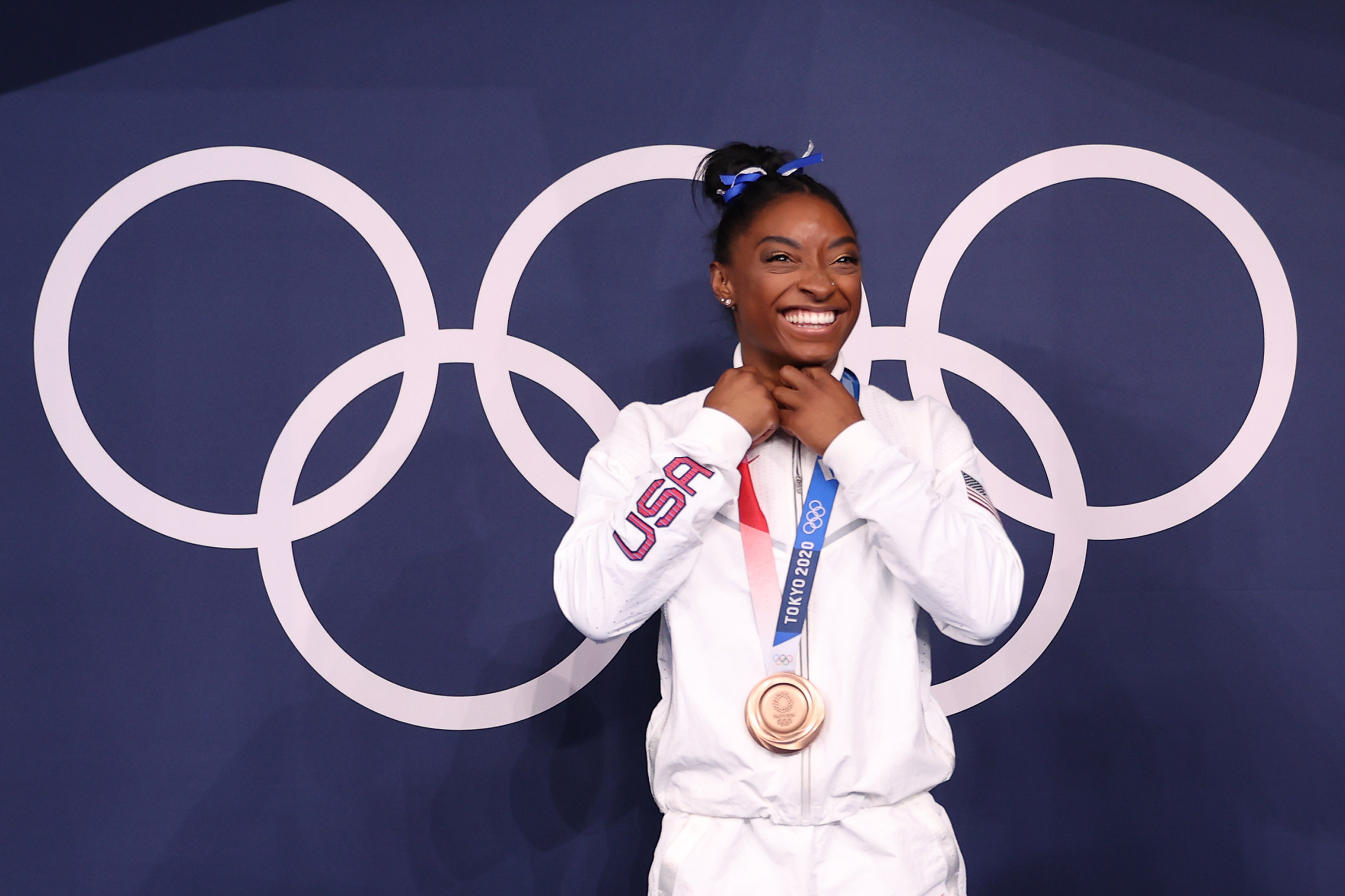 Biles poses in front of the Olympic rings with her bronze medal around her neck