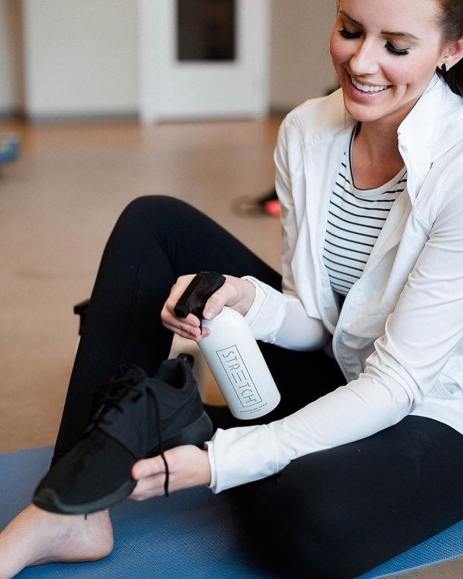 A smiling person misting their running shoes with the fabric spray
