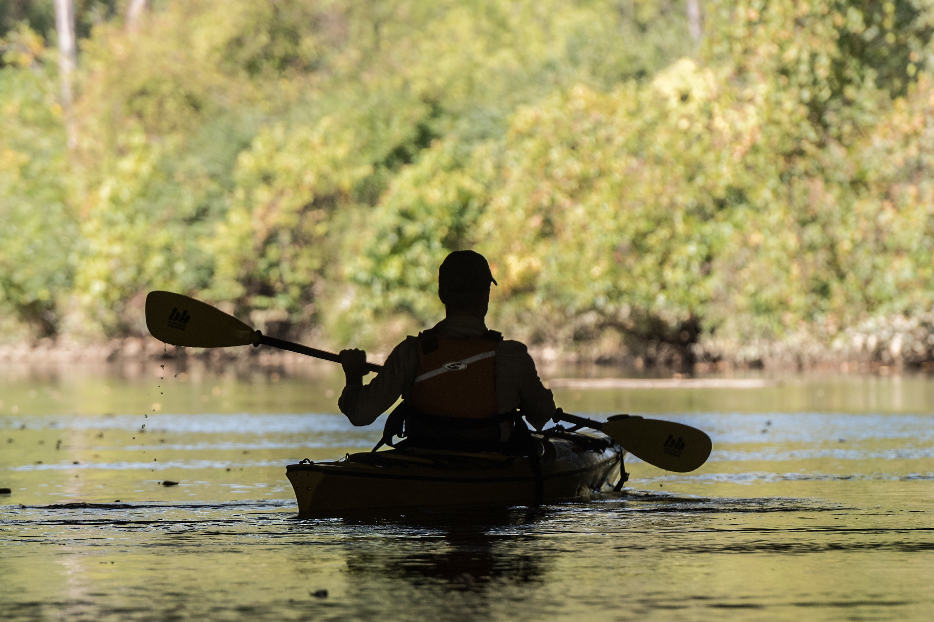 A person with a hat paddles through a body of water in Indiana Dunes Park.