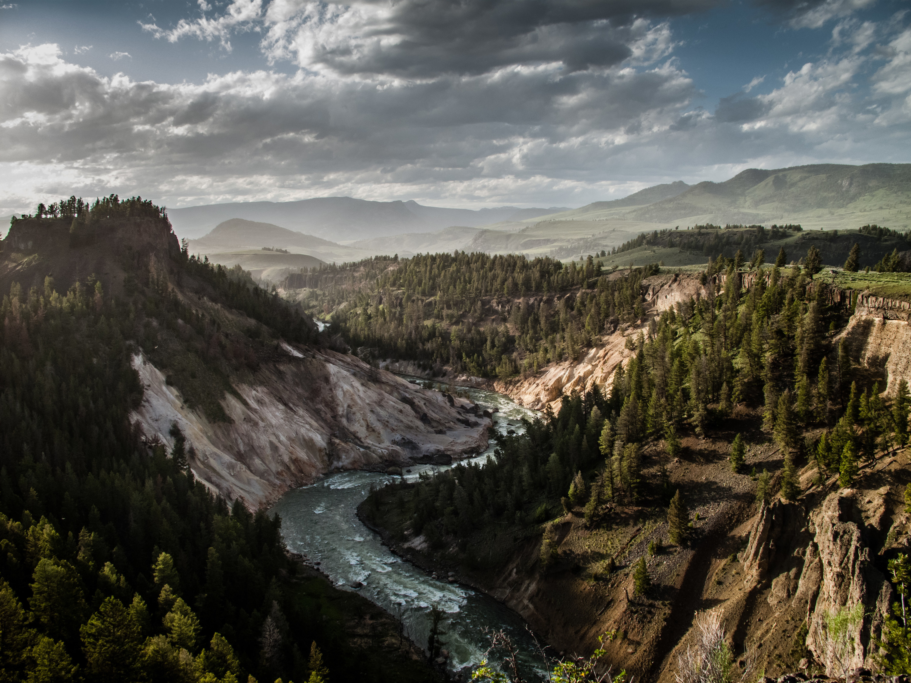 A river courses through the jagged canyon of Yellowstone National Park while clouds loom above.