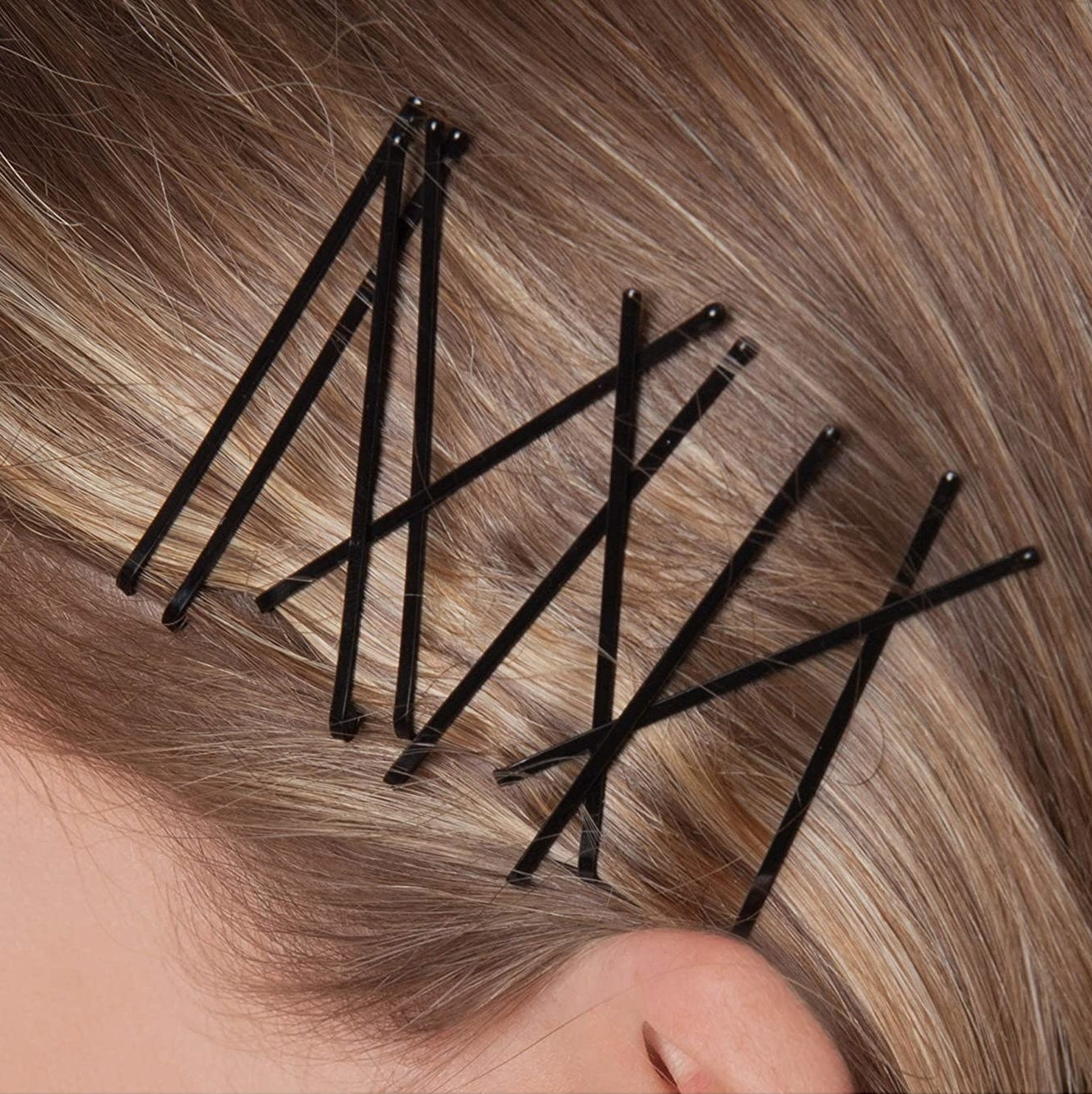 A person with several bobby pins in their hair