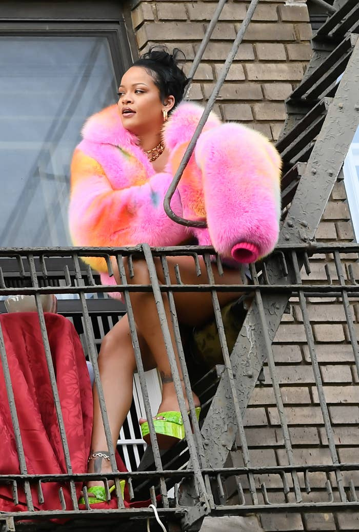 Rihanna is pictured on a fire escape in the Bronx while filming a music video in July of 2021