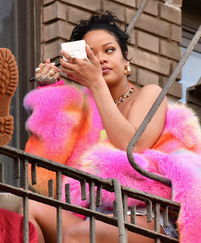Rihanna is pictured applying makeup on the set of her music video