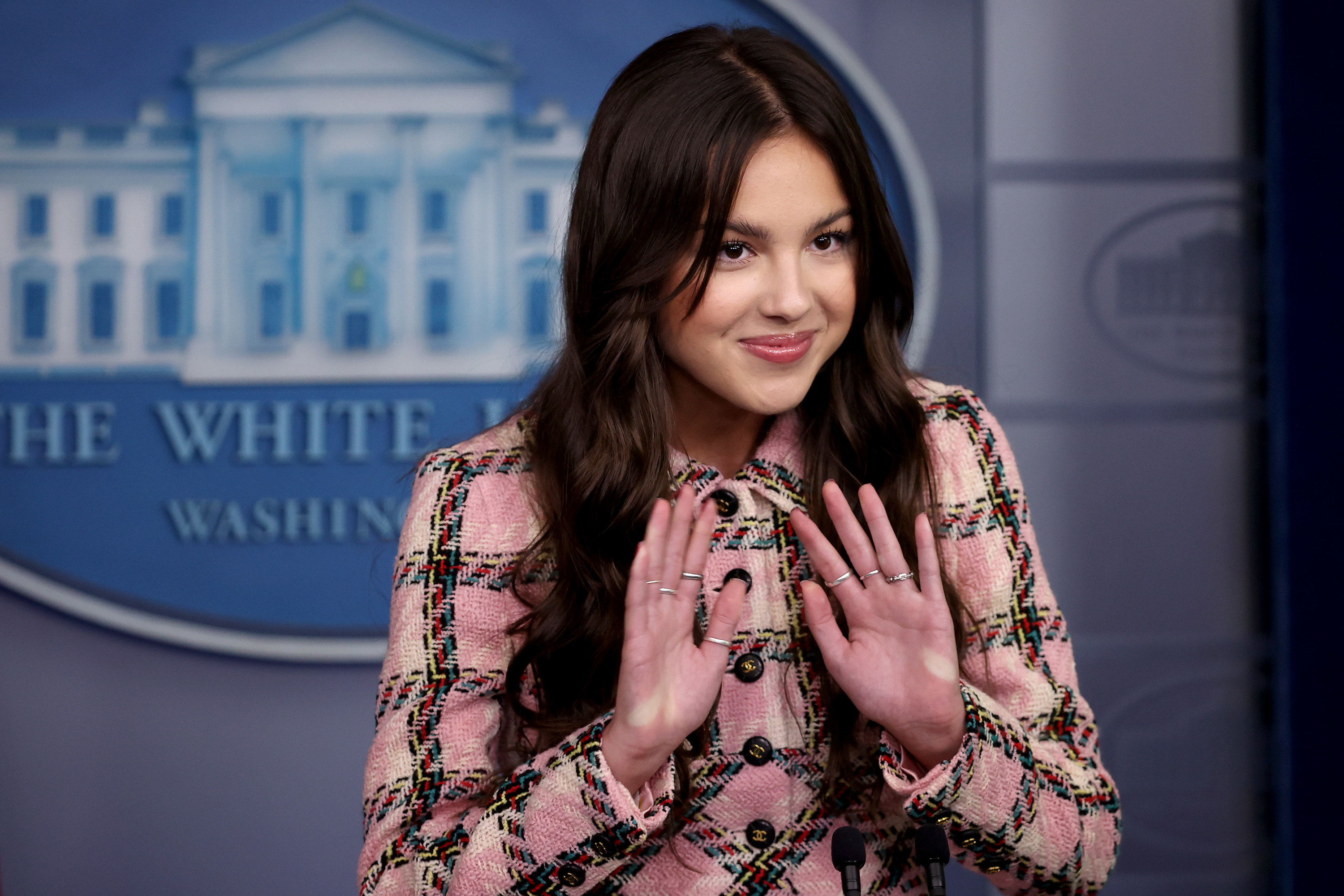 Olivia speaking in the White House press room in a plaid outfit
