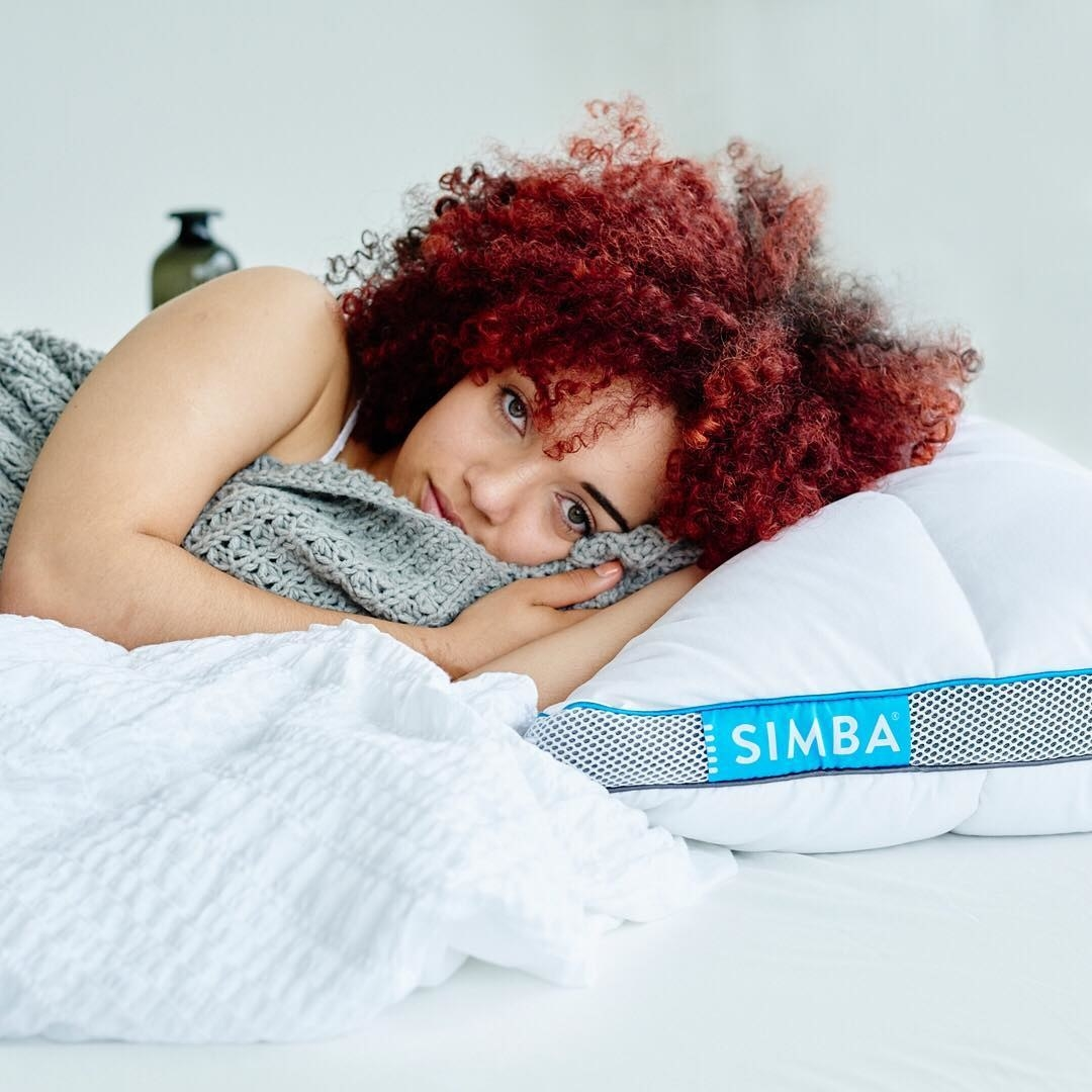 A person looking into the camera while laying on one of the hybrid pillows
