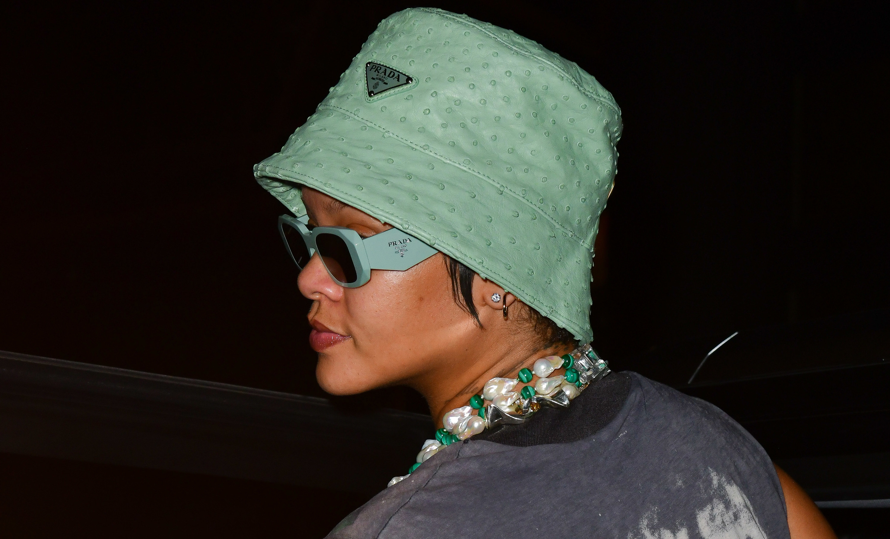 Rihanna is photographed wearing a green hat and sunglasses in New York City