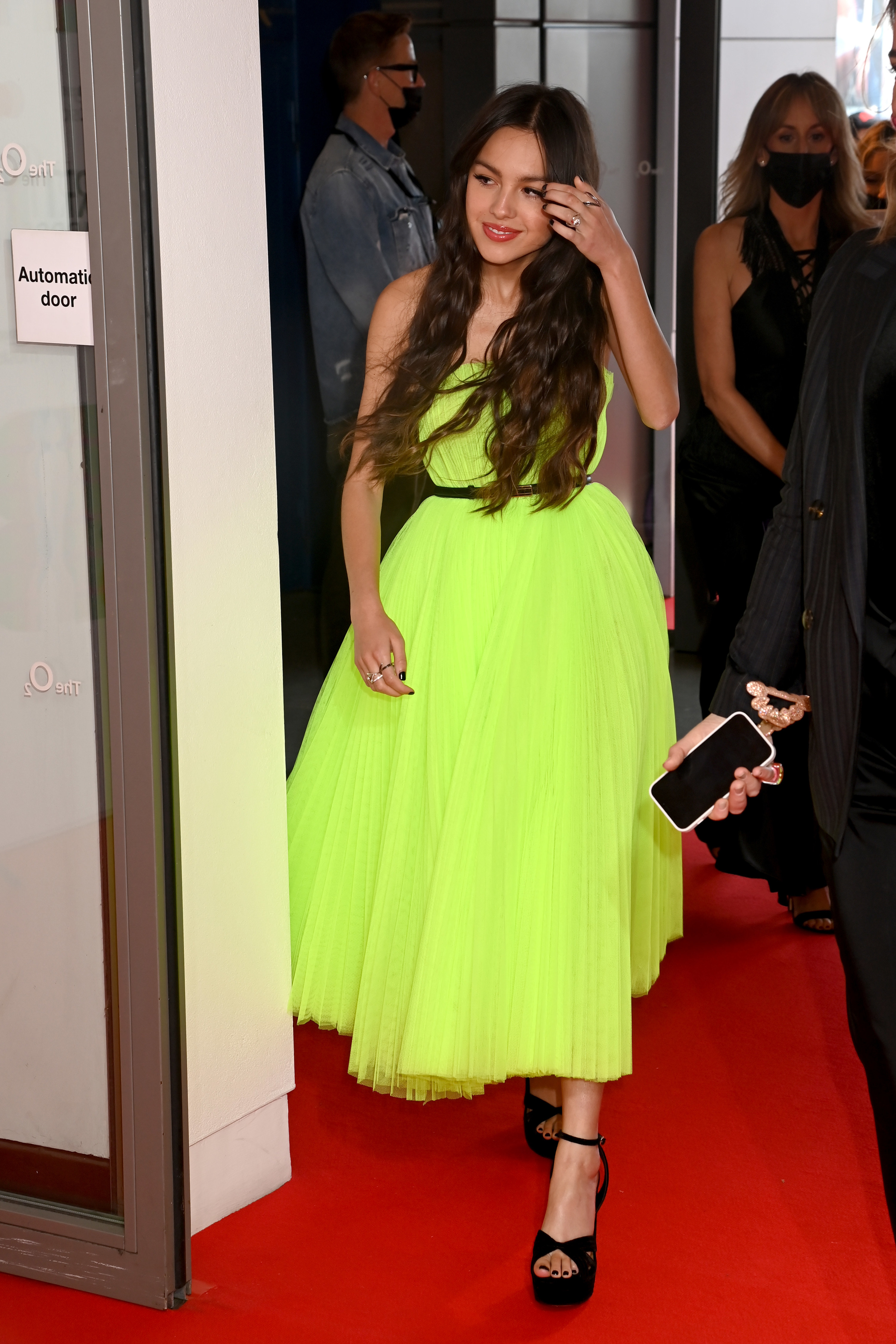 Olivia in a brightly colored flared dress at an event