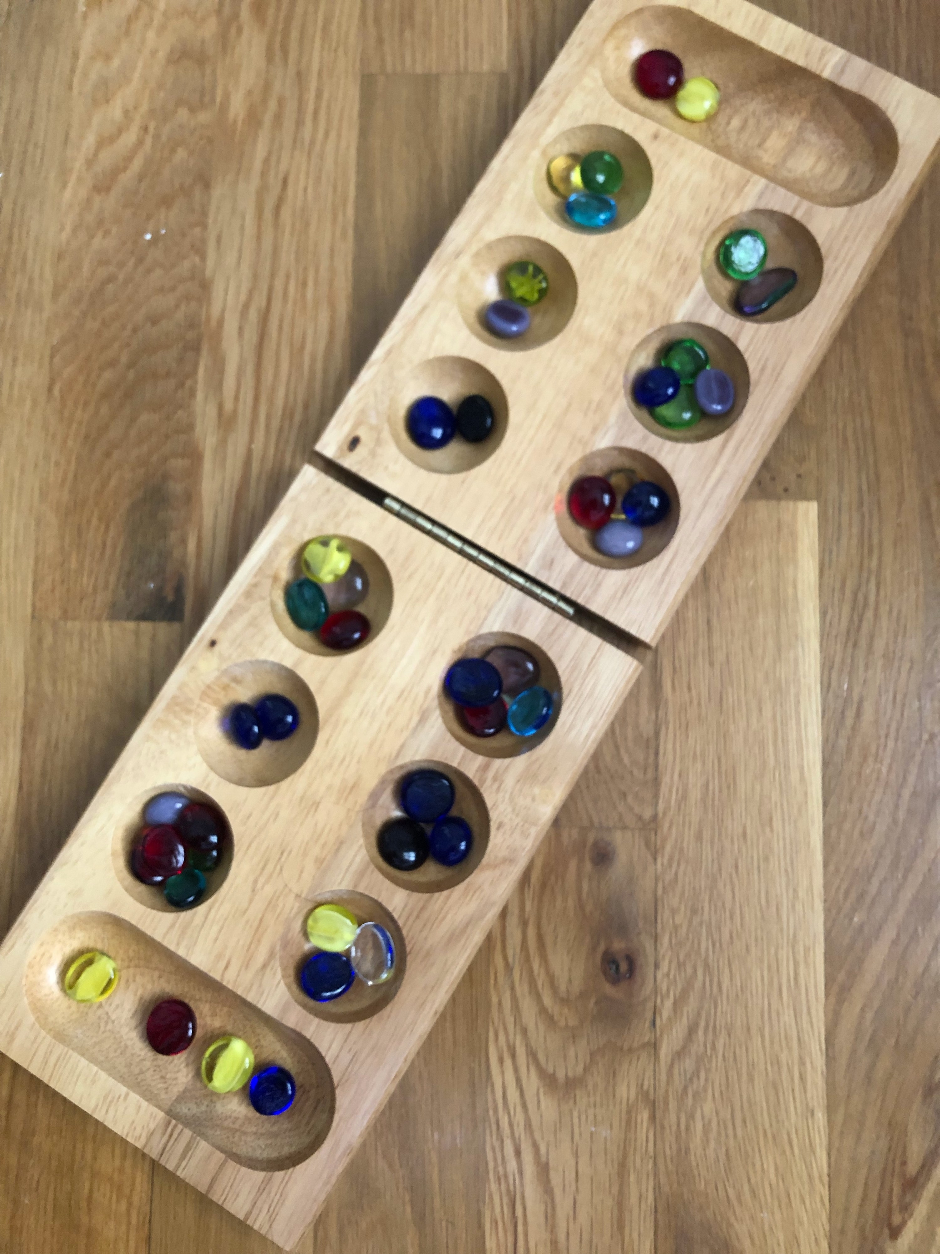 Mancala board filled with colorful marbles in every pocket