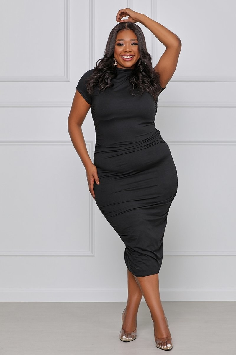 model wearing the mid-calf length short-sleeved rouched dress in black