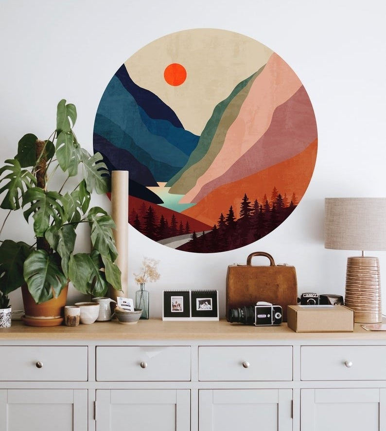 a round, vibrant wall decal with a forest and mountain illustration on a wall above a dresser