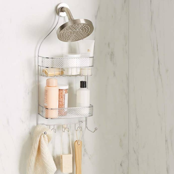 A cage shower caddy with two wire baskets and hooks for hanging storage hung on a shower head