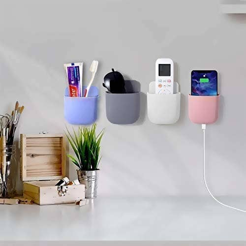 4 wall mount storage cases in different colours holding a remote, sunglasses, a charging phone and a toothbrush and toothpaste