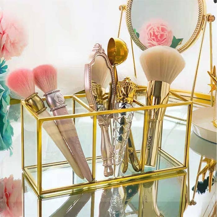 A clear glass bathroom organiser with a golden metal trimmings and 3 compartments