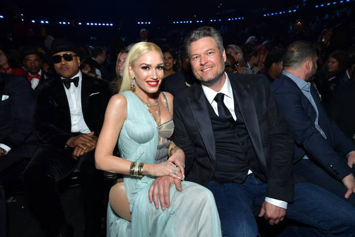Gwen, in a gown, and Blake, in a suit smiling for the camera at an awards show with LL Cool J in the background