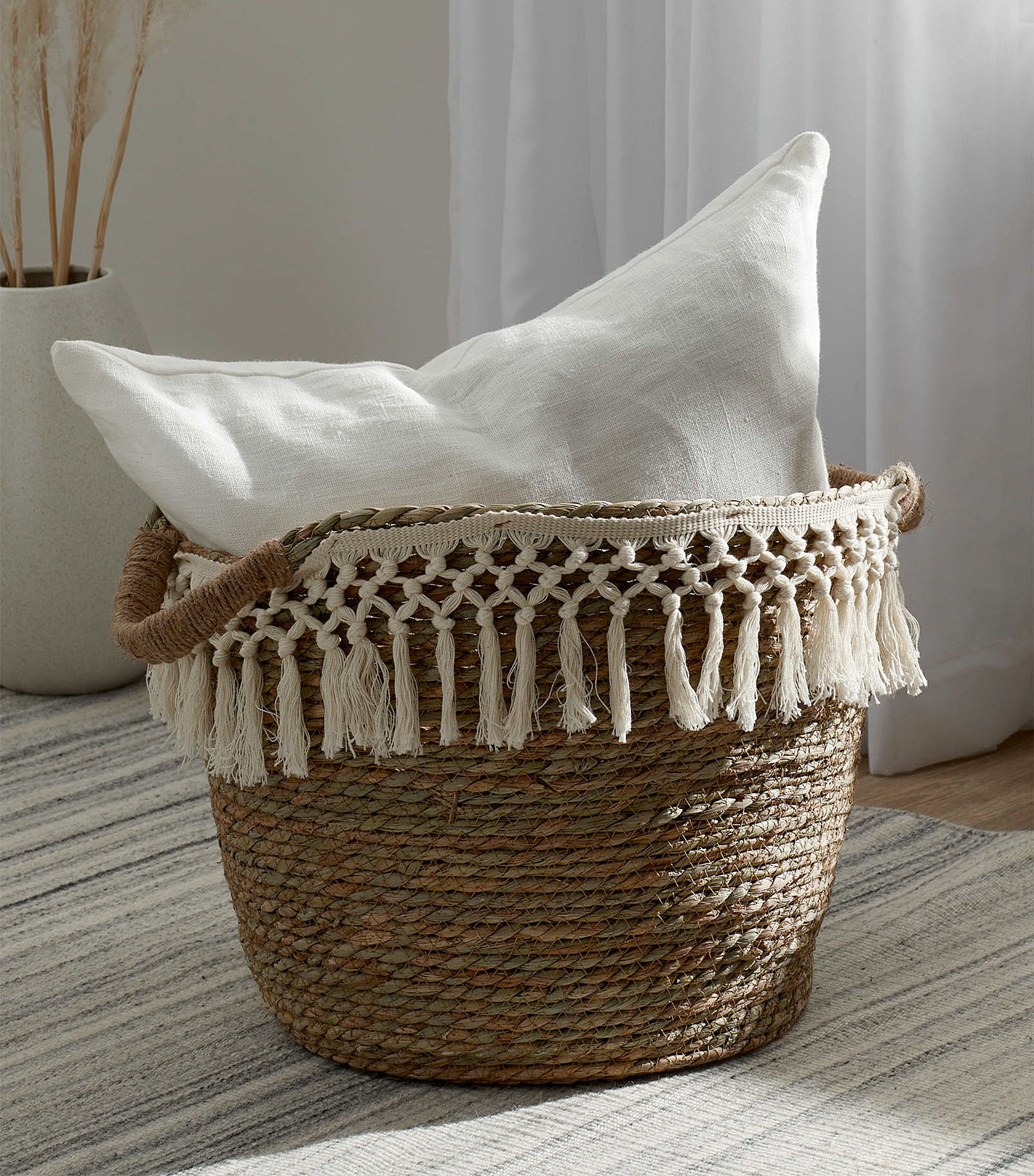a stylish basket with a macrame fringe around the top and a pillow inside