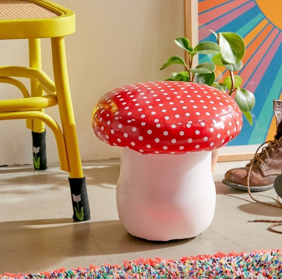 a stool with a white bottom and red polka-dot top that looks like a mushroom