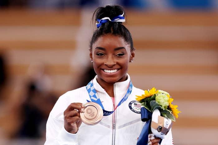 Simone holding her bronze medal