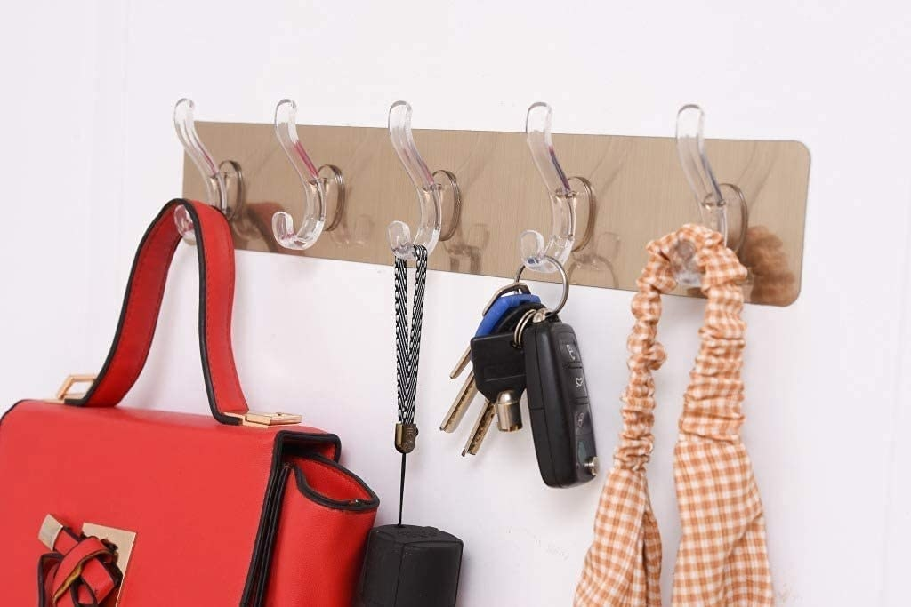 A stainless steel self adhesive string with 5 plastic & transparent hooks with different products hanging on them