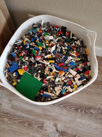 Reviewer's up-close photo showing the brown and beige rope basket holding legos