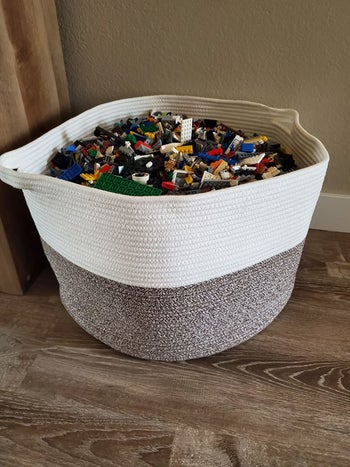 Reviewer's photo showing the brown and beige rope basket holding legos