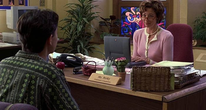 Ms. Perky addresses cameron in her office wearing pink sweater and pearls