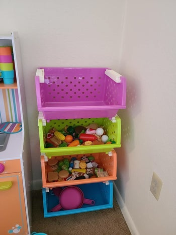 Reviewer's photo showing the multicolored organizer with four bins holding toys