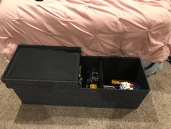 Reviewer's photo showing the dark grey ottoman at the foot of their bed with the lid open to reveal toys
