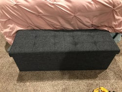 Reviewer's photo showing the dark grey ottoman at the foot of their bed