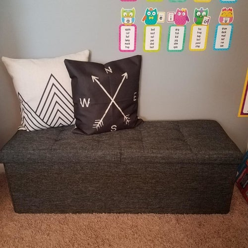 Reviewer's photo showing the dark grey ottoman decorated with cushions in their kid's playroom