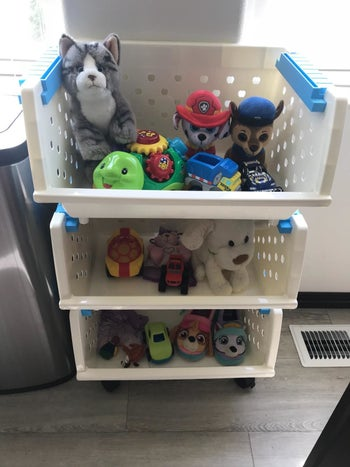 Reviewer's photo showing the white organizer with three bins holding toys and stuffed animals