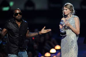 Kanye West stands with both arms outstretched as Taylor Swift stands beside him with a confused look on her face