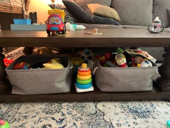 Reviewer's photo showing the grey bins holding toys under their coffee table