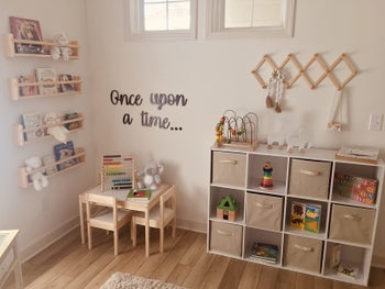 Reviewer's photo showing the beige fabric storage cubes in their shelving unit in the playroom