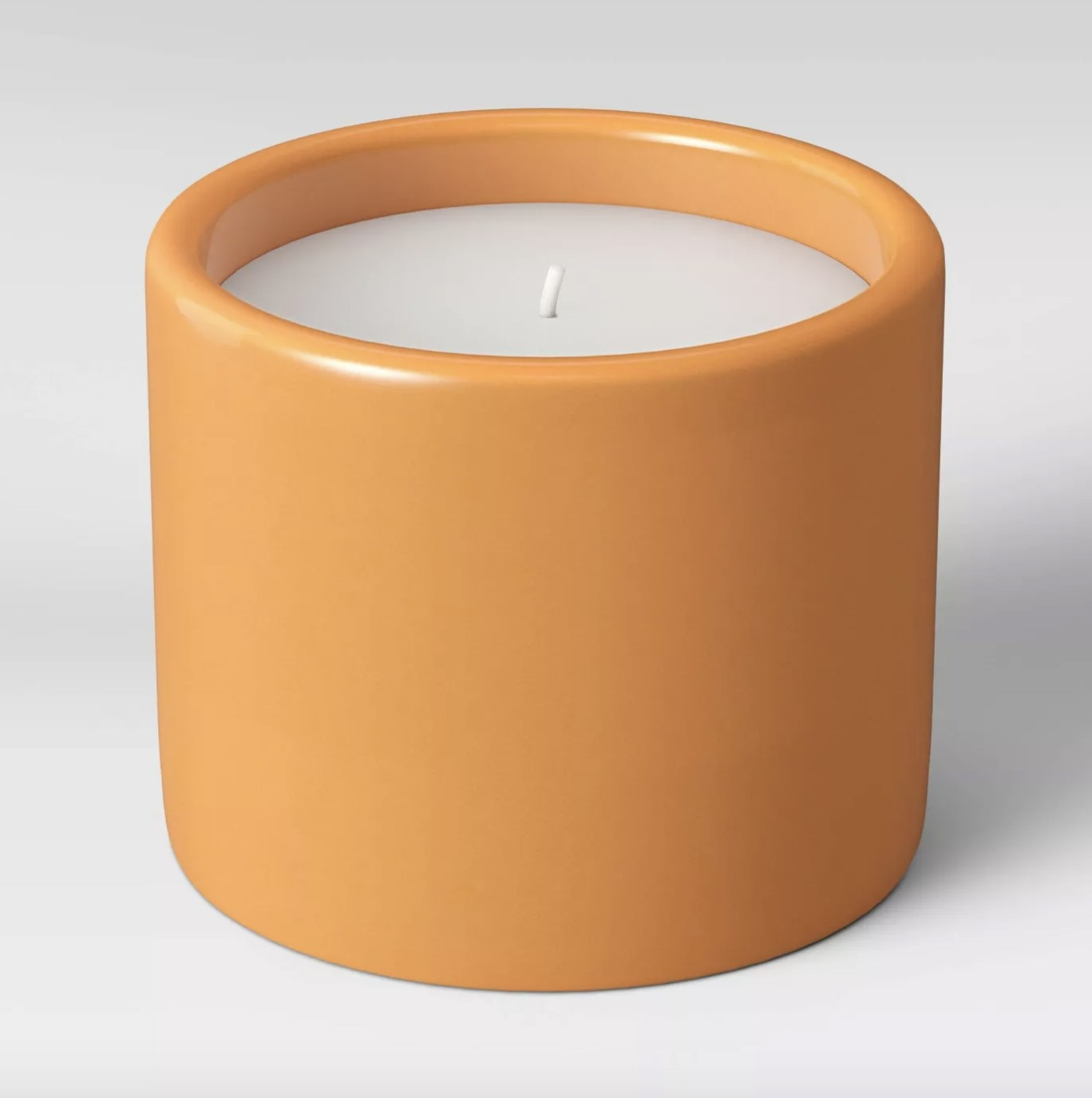 The cylindrical candle holder is in the sun orange color and has a white candle inside