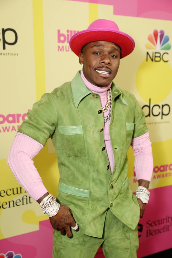 DaBaby smiles for the camera while wearing a hat, suit, and sweater with multiple pieces of jewelry on both wrists