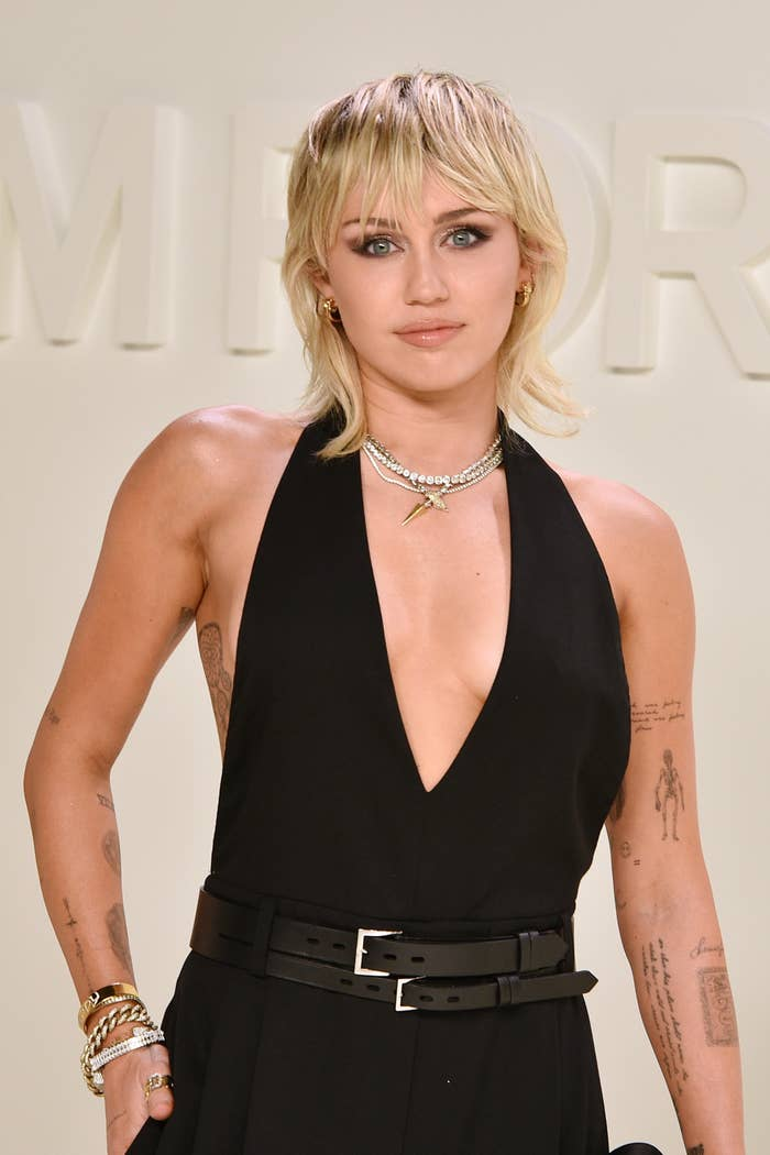 Miley Cyrus poses at a fashion event while wearing a dress with a belt around it