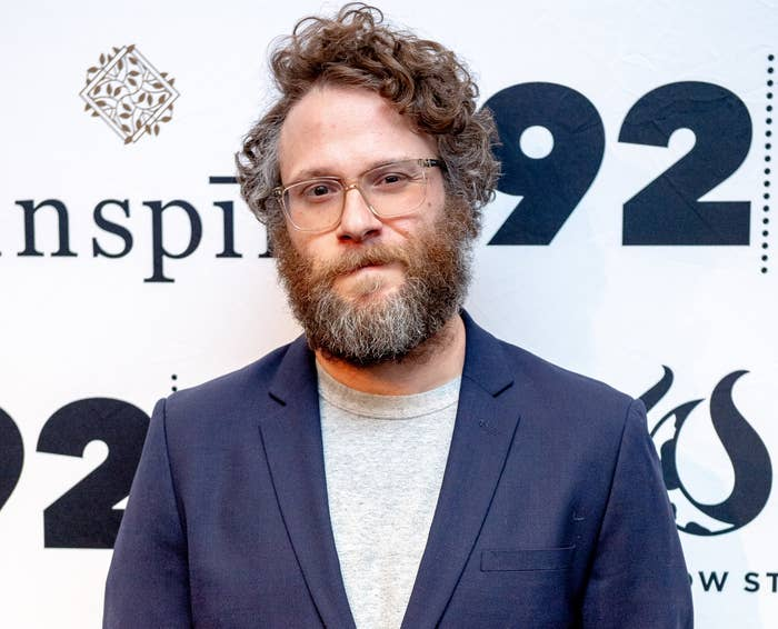 Seth has a scruffy beard and wears clear glasses, a navy suit jacket and grey t-shirt