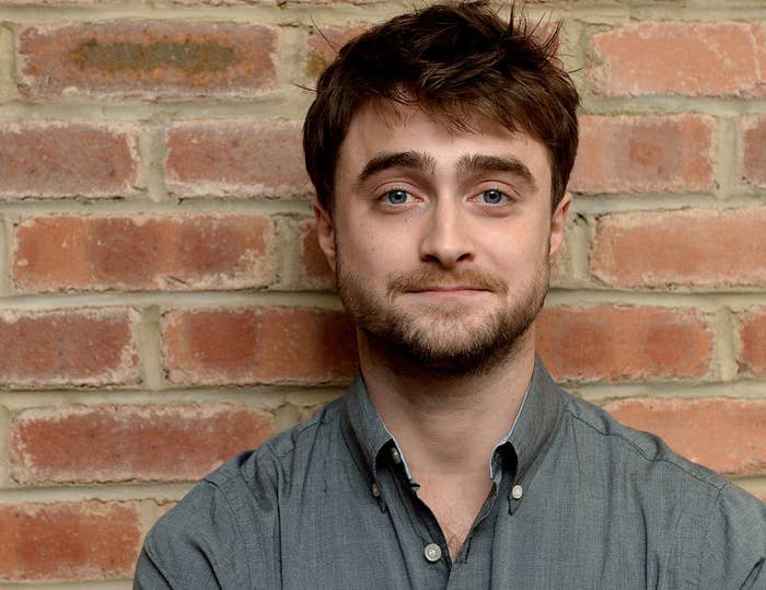 Daniel Radcliffe standing against a brick wall for a photograph