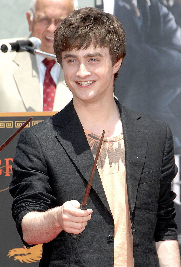 """Daniel Radcliffe holds a wand and smiles at the """"Harry Potter and the Order of the Phoenix"""" - Hand, Footprint and Wand ceremony"""