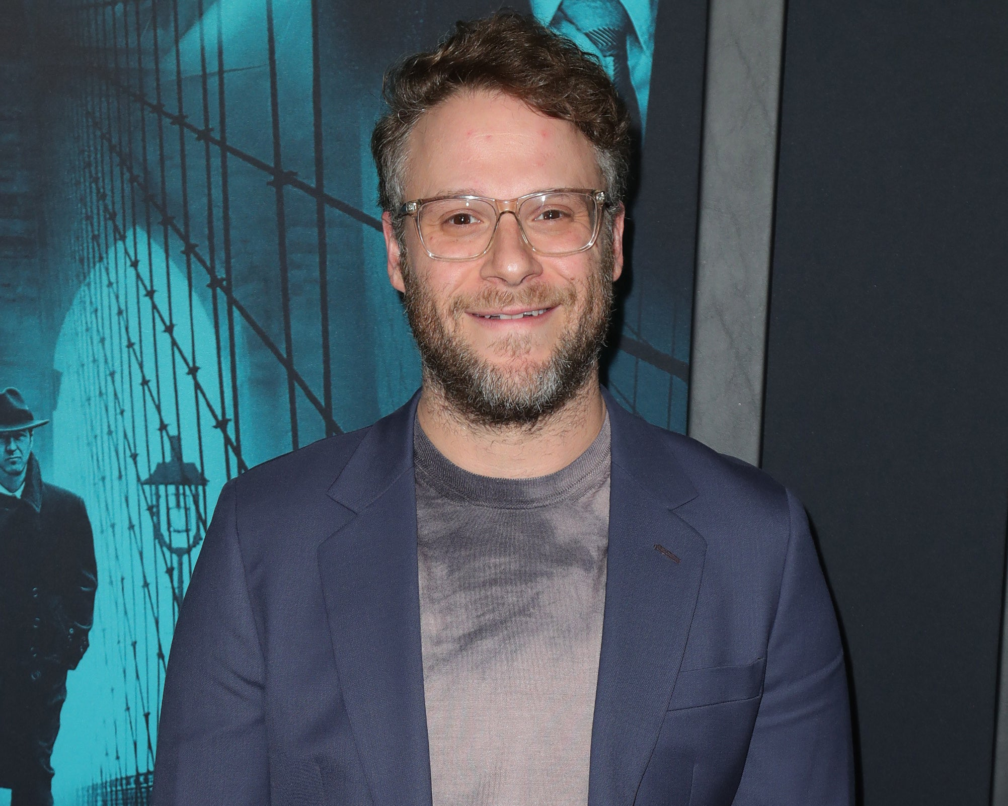 Seth smiles while wearing a blazer and grey tie dye t-shirt